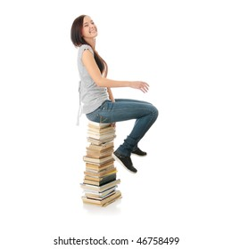 Young teen woman sitting on books isolated on white background