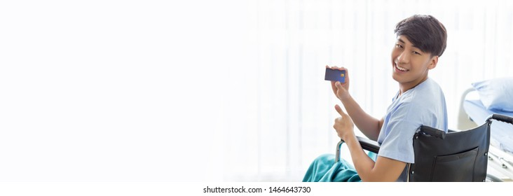 Young teenage Asian man holding credit card sitting on the wheelchair in the hospital with smiley face.