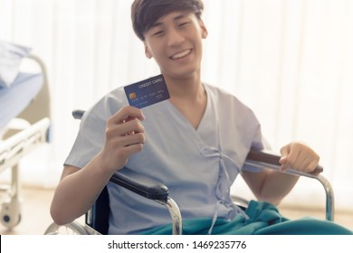 Young teenage Asian man holding credit card sitting on the bed in the hospital with smiley face.