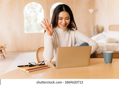 Young teenage Asian woman wear sweater with pretty smile waving at someone in laptop in cozy room. Happy and stylish girl video calling and conferencing. Winter business portrait lifestyle. Copy space