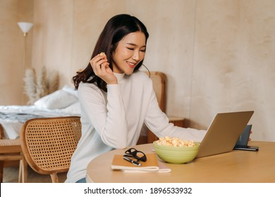 Young teenage Asian woman wears sweater with pretty smile in bed room. Happy smiling girl using laptop with notebook watching movies, films, videos online. .Online technology concept