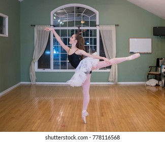 Young teenage ballet dancer wearing a white petticoat, black leotard and reindeer ears poses in a dance studio