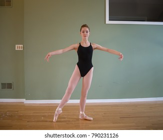 A young teenage ballet dancer wearing pointe shoes, tights and a black leotard standing in tendu in second position