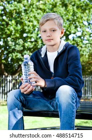 Young teenage boy with bottle of water in park sitting on the bench