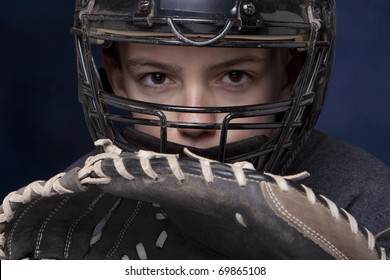 Young teenage boy in catcher's mask with glove ready and dramatic dark blue background.