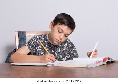 Young teenage boy doing his homework and using his phone