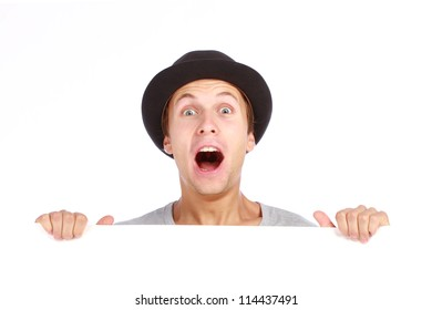 Young teenage boy hiding behind a billboard and making a face on camera isolated on white background