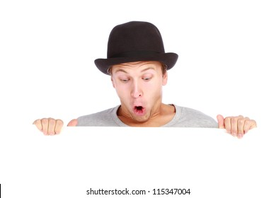 Young teenage boy hiding behind a billboard and making a face looking down isolated on white background