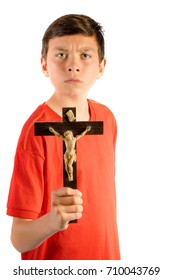Young teenage boy isolated against white holding a crucifix