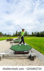 Young teenage boy outdoors at a driving range playing golf and practice his swing.