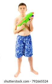 Young teenage boy playing with water guns isolated on a white background
