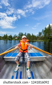 Young teenage boy rowing a rowboat on a lake with blue summer sky in the background.