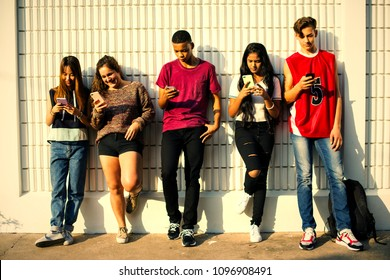 Young teenage friends chilling out together and using smartphones