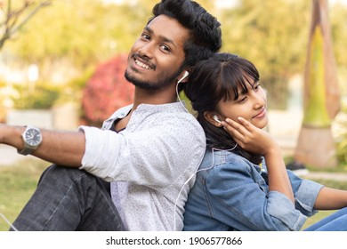 Young teenage friends enjoying listening to favorite song or music by Sitting back to back at college - Concept of couple relaxing, picnic in park, Love,dating, romance and modern millennial lifestyle