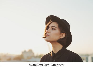 A young teenage girl in a black shirt and hat looks melancholy in the sky. The style of the big city. Sunset sky and rays of the sun. Thought over the problems of adulthood