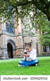 Young teenage girl busy with texting by smartphone sitting on the grass in Glasgow University garden. Scotland, UK. Summertime outdoors vertical image.