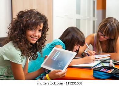 Young teenage girl with classmates showing homework on digital tablet.
