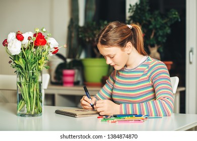 Young teenage girl drawing at home, sitting at the table