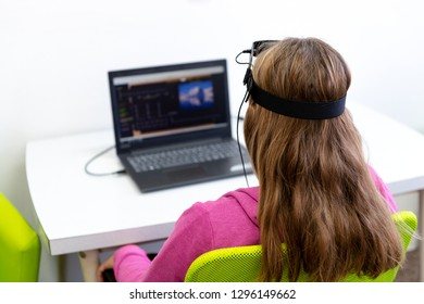 Young teenage girl during EEG neurofeedback session. Electroencephalography concept. Back view.
