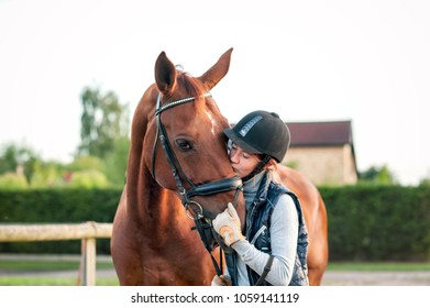 Young teenage girl equestrian kissing her favorite red horse. Multicolored outdoors horizontal image.