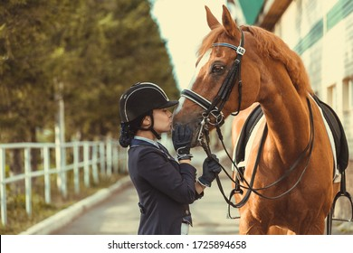 Young teenage girl equestrian kissing her favorite red horse. Multicolored outdoors horizontal image. Dressage outfit
