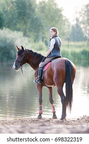 Young teenage girl equestrian riding horseback to river at early morning in rays of sunlight. View from backside. Multicolored outdoors vertical summertime slightly filtered image with backlight