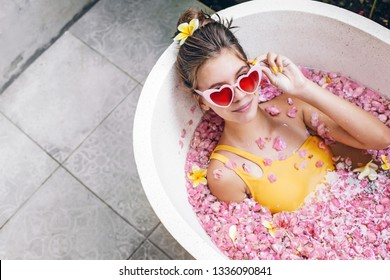 Young teenage girl in funky heart shape sunglasses relaxing in organic bath tube with tropical flowers in luxury Bali spa resort