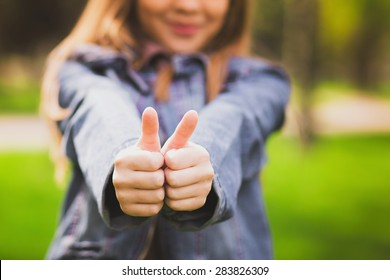 Young teenage girl giving thumb up as sign of success. Portrait of happy smiling anonymous caucasian child dressed in blue jeans casual clothing. Focus at hands.
