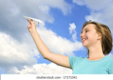 Young teenage girl holding a paper airplane