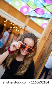 A young teenage girl looks over her sunglasses and smiles at an open-air market.