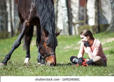 Junge Teenagermädchenbesitzerin sitzt neben ihrem Kastanienpferd auf grünem Gras. Lebhaftes, mehrfarbiges Frühling im Freien, horizontales Bild.