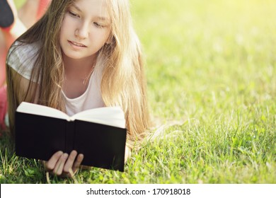 young teenage girl reading book on grass, summertime lifestile