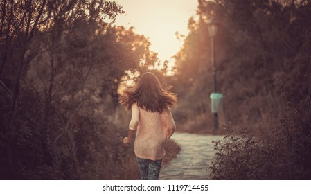 Young teenage girl running along a lonely cobblestone path, enjoying a beautiful sunset in nature