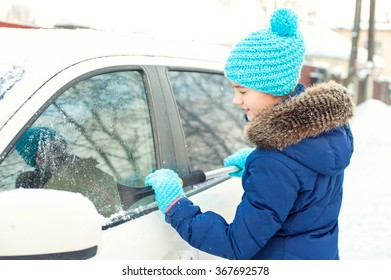 Young teenage girl scraping ice on car window from winter snow in january. Bright outdoors horizontal image