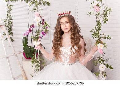 A young teenage girl sits on a swing among the flowers in the studio on a light background in a sumptuous white dress and a magnificent crown. Princess with long wavy hair. Queen beauty contest