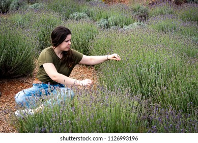 Young teenage girl sitting and enjoying the beautiful fresh lavender herbal plant