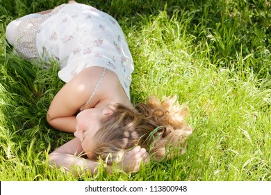 Young teenage girl sleeping while laying down on long green grass in a garden during the summer.