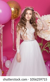 A young teenage girl stands in the studio amid balloons and flowers in a sumptuous white dress and a magnificent crown. Princess with long wavy hair. Queen beauty contest