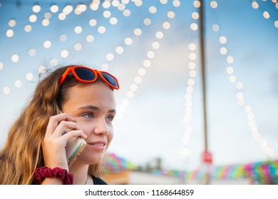 A young teenage girl talks on her mobile phone at an open-air flea market