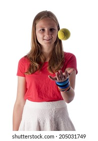 Young teenage girl throwing a tennis ball in the air over a white background