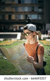 Young teenage girl traveling and using map for orientation