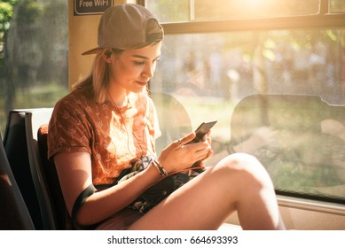 Young teenage girl using her cell phone in public transportation