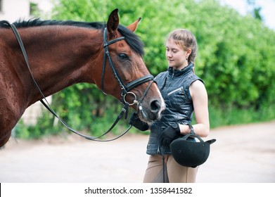 Young teenage lady leads and tenderly looking at her favorite red horse. Vibrant colored outdoors horizontal summertime image.