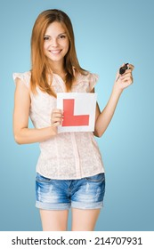 Young teenage learner driver holding L-plate and car keys.