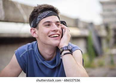 Young teenage man having a pleasant conversation on his phone
