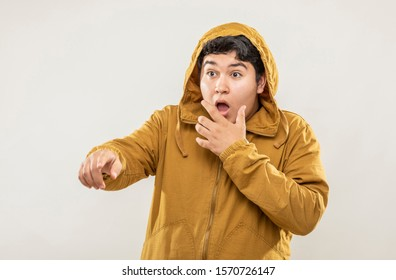 Young teenage man with yellow sweatshirt with surprised face expression on gray background.