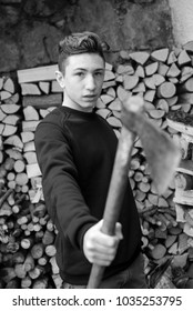 young teenager with axe in hands - black and white photo