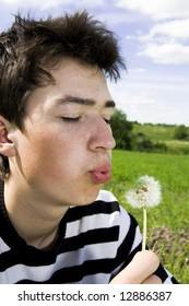 Young teenager blowing dandelion at sunny day