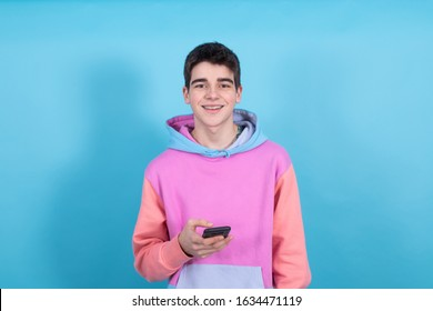 young teenager boy with mobile phone isolated on blue background