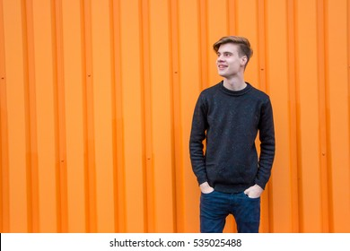Young teenager boy posing over bright orange contrast background looking aside with happy smile; portrait with copyspace